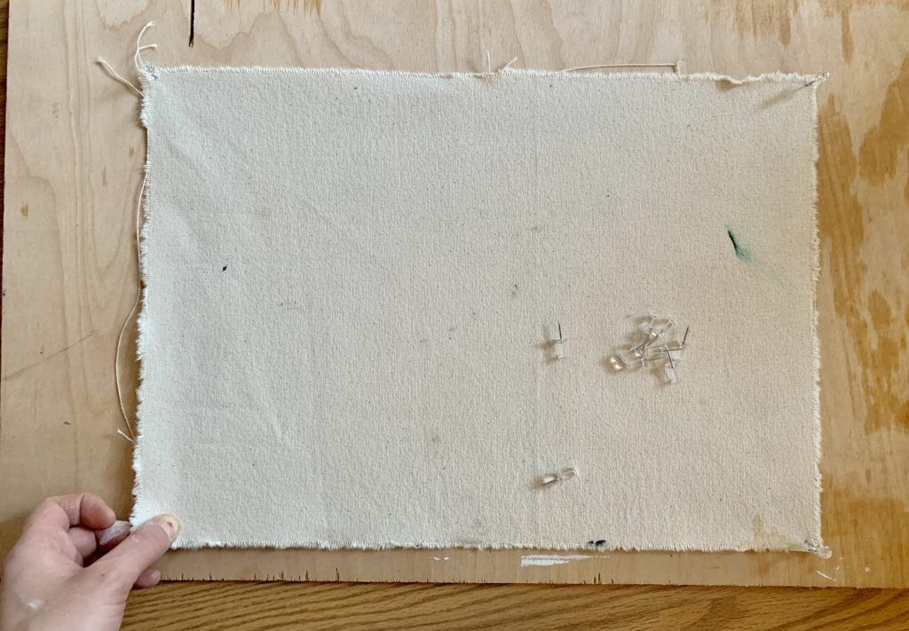 A hand holds a corner of a piece of canvas while pinning it to a wood panel
