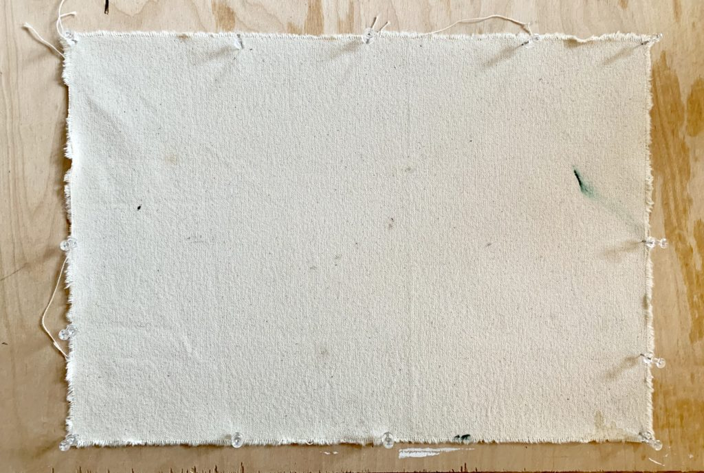 A piece of canvas pinned to a board ready for gesso paint to be applied