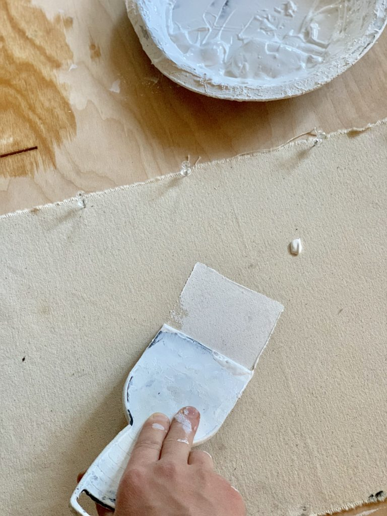 Applying first gesso primer for canvas