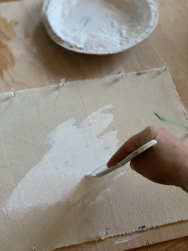 Artists hand holding a tool gesso priming a piece of canvas