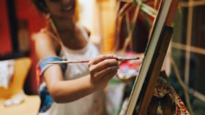 Artist with paint brush showing oil painting tips for beginners