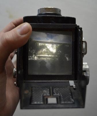 a hand holding a box camera