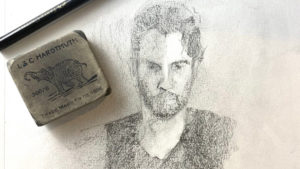 Sketch of a man with an eraser and pencil lying on top of the paper