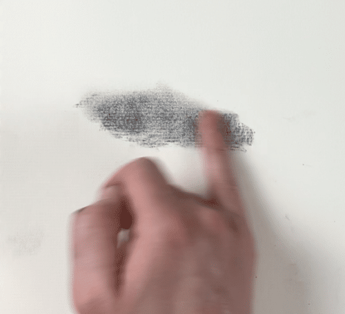 using a finger to create soft edges in a charcoal drawing