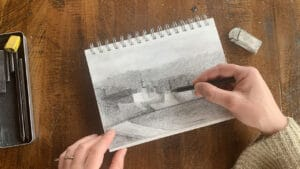 an artist sketching ideas in a sketchbook