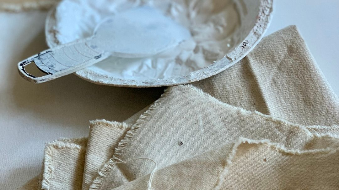 gesso primer in a bowl laying next to canvas