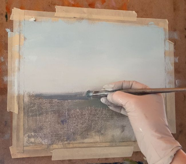 Artist with a brush showing how to paint an ocean starting to paint the water