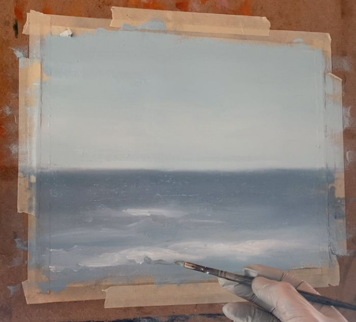 a hand with a paint brush painting waves in an ocean painting