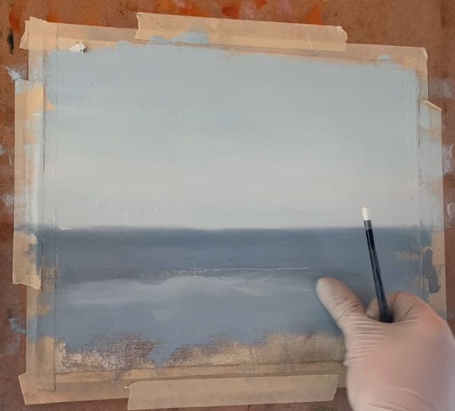 artist using thumb to blend white color in a seascape painting