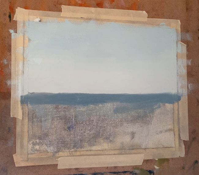 painting of an ocean started, with a bit of the ocean and sky painted in