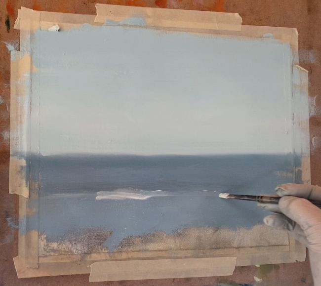 artist with a brush in hand starting to paint ocean waves in a sea