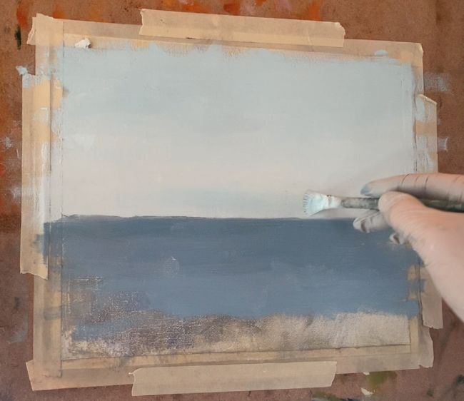 hand with brush painting the horizon line above an ocean painting