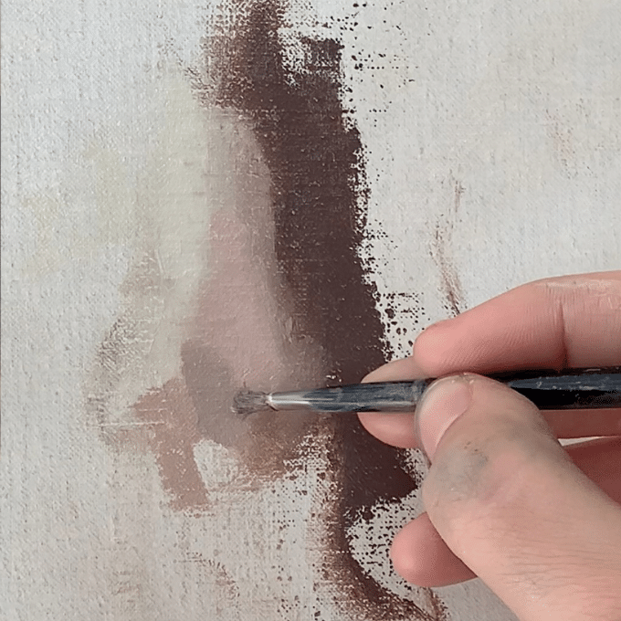 artist's hand painting a nose with paint brush