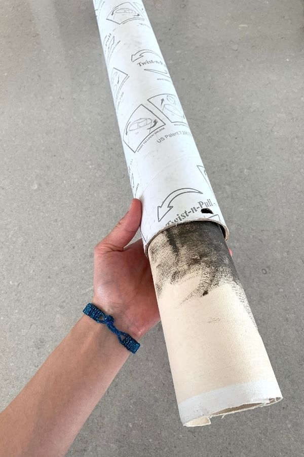 an artist holding a mailing tube that is being used as an art supply carrying case