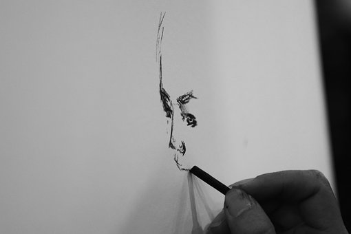 an artist's hand drawing a face with charcoal creating a value drawing study before starting an oil painting