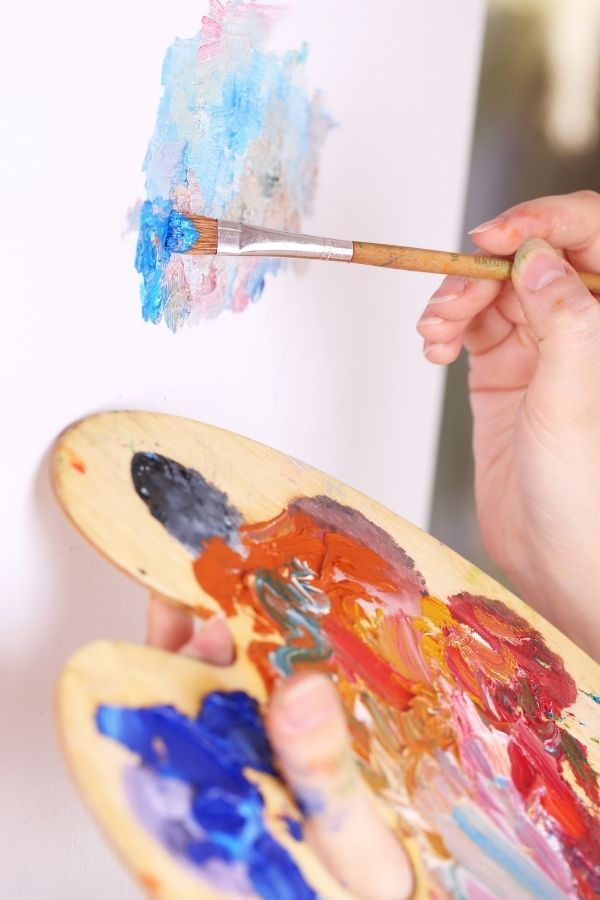 artist with brush showing how to start and oil painting with a big paint brush and plenty of paint on her palette