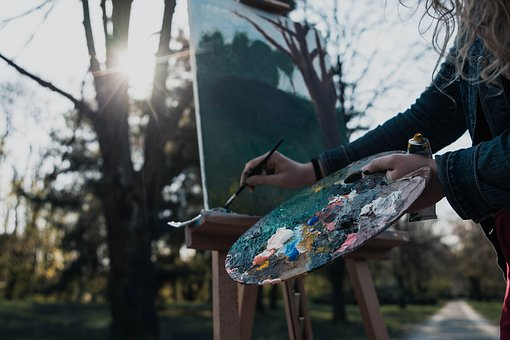 a woman holding a palette and brush working on a landscape oil painting for beginners outdoors