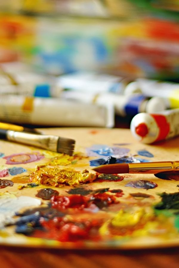 Oil painting art supplies such as paint, brushes and palette for beginners, laid out on a table