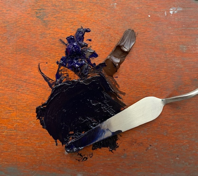 A palette knife mixing colors on a palette board, to use for a painting sketch