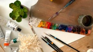An array of painting ideas lying on a white table with an artist's paint brushes and palette