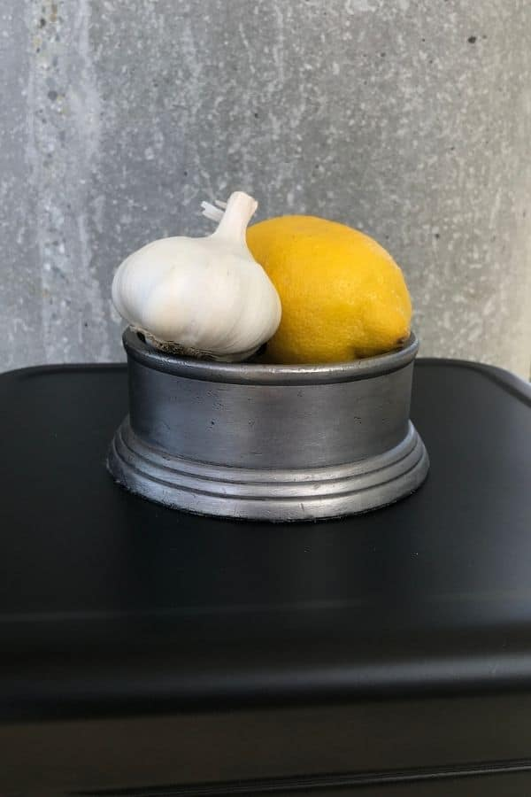 still life simple painting idea of a garlic and lemon together in a shiny container on black surface