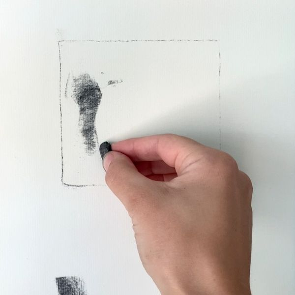artist creating a thumbnail drawing with charcoal on white drawing paper