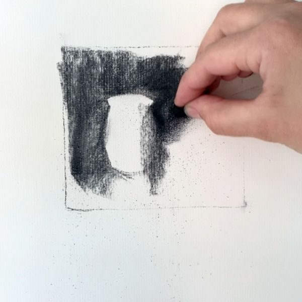A hand drawing shadow areas in a vale drawing study