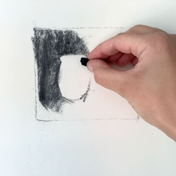 artist drawing with charcoal for value sketch
