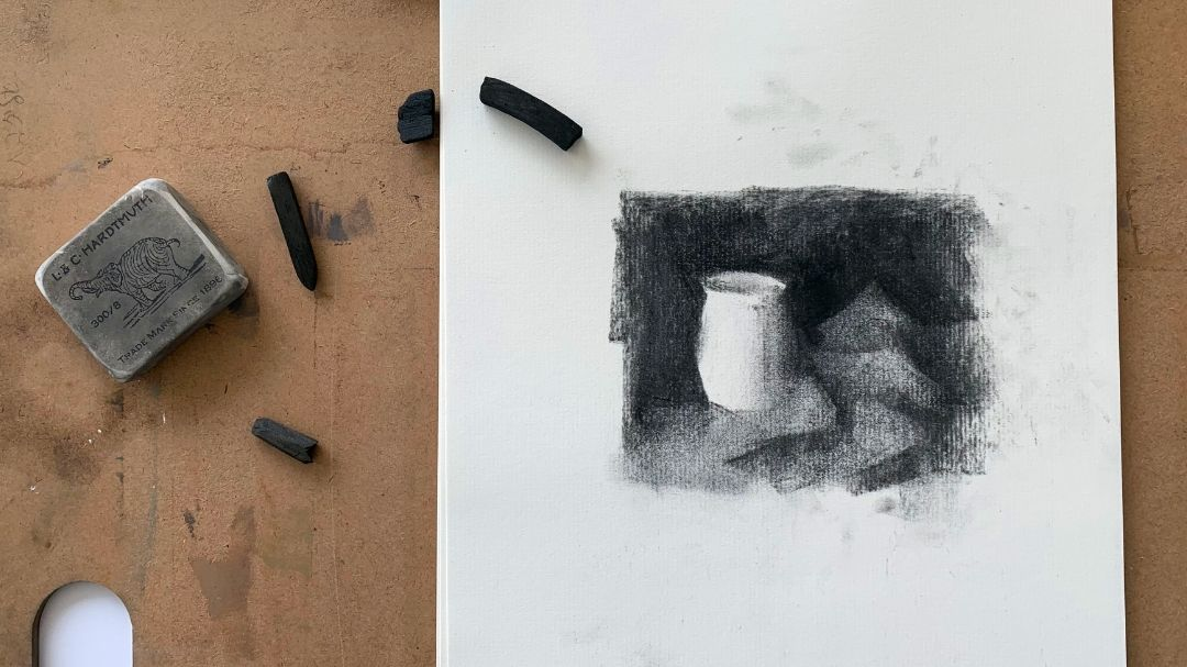 Thumbnail sketch on paper laying on an artist's palette with pieces of drawing charcoal scattered around