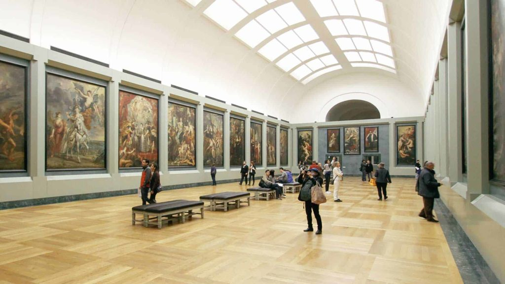 an art gallery hall with skylights showcasing numerous large painting on the walls