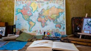 A map of the world on a table with travel art supplies lying around it