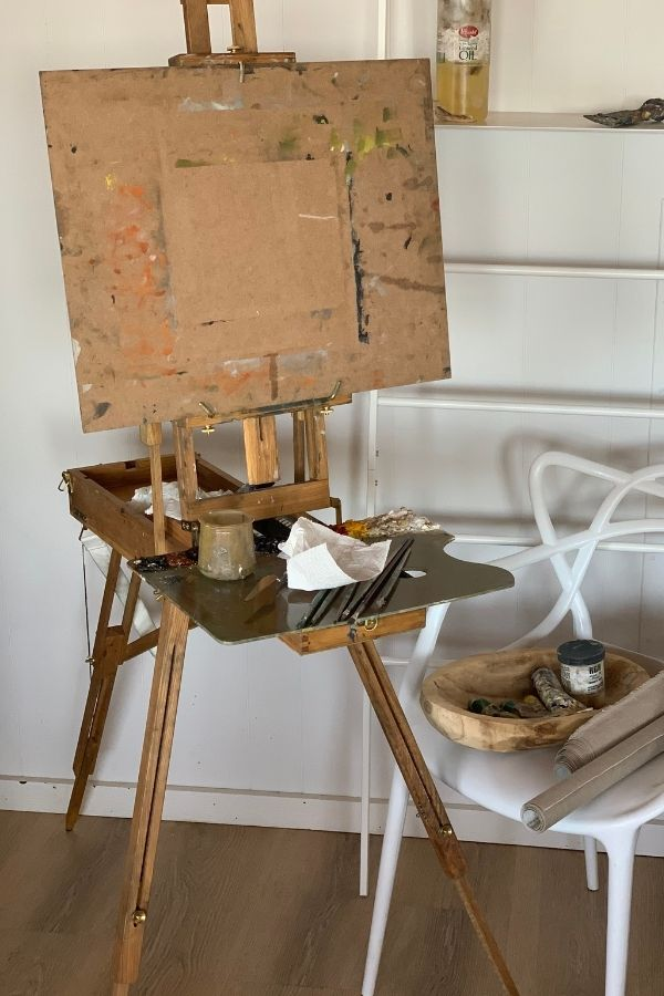 Travel easel in a room with art supplies on the easel's palette tray