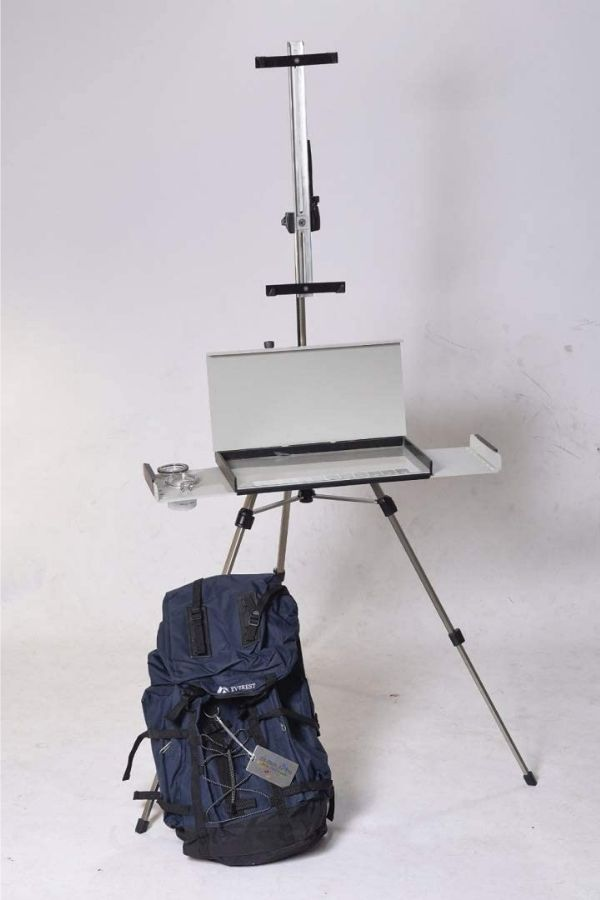 tripod easel with palette box tray pictured in a white room and a blue travel case resting on the floor
