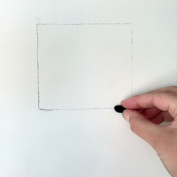 artist beginning to draw a square box with a piece of drawing charcoal
