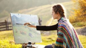 girl mixing fall paint colors for a fall landscape painting